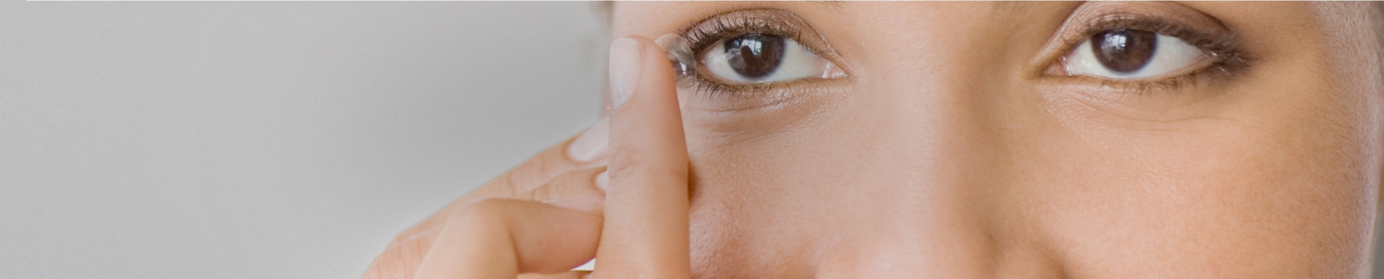 Close-up of a young woman with her contact lens on her fingertip about to put it in her eye