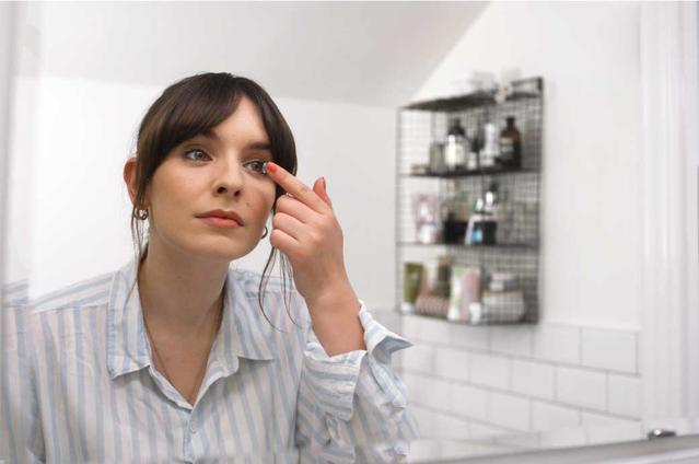 Girl putting in contact lens