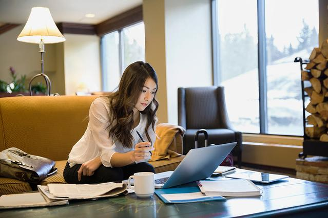 A woman at her desk in the office looking at a notebook