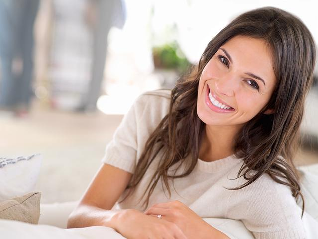 Adult woman smiling as she sits on the sofa