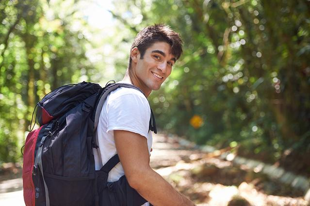 A man with a backpack in the middle of the forest.