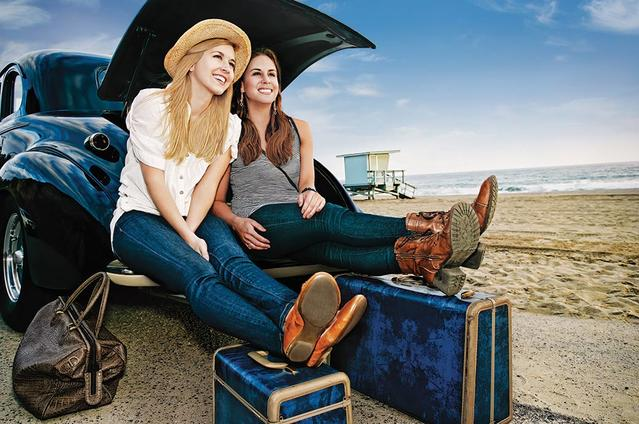 Two girls sitting on the trunk of a car by the beach with their luggage ready to travel