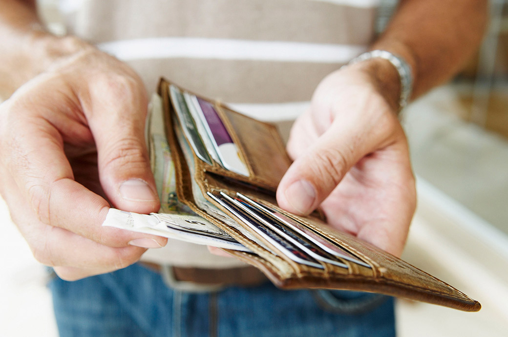 A close up of a man holding a wallet and pulling money out
